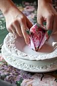 Hand hält gefaltete Serviette mit Blumenmuster auf weißem Gedeck mit Prägemuster