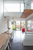 Two wooden table and white chairs in modern, open-plan interior with gallery