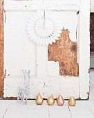 Holzwand im Shabbystil, davor gold- und kupferfarbene Dekobirnen und ein weisses Rentier