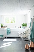 Copper vases on grey-tiled floor, retro cord chairs next to bathtub below window in modern, white bathroom