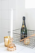 White candles in gilt candlestick and gold tealight holders in front of bottle of Champagne in wire basket