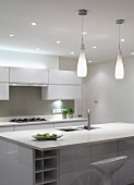 Bottle-shaped pendant lamps above sink unit with breakfast bar in designer kitchen