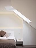 Gestrickte Kissen und Decke in Naturfarben auf dem Bett in puristischem Mansardenzimmer, Einbauschrank in der Dachschräge