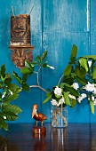 Carved pelican figurine and flowering branches in vase below wooden ethnic carvings on wall painted light blue