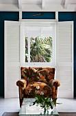 Armchair with brown, retro floral pattern and wicker table with glass top in front of French window with interior folding shutters