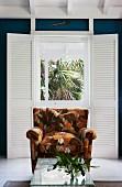 Sessel mit braun floralem Retromuster und Korbtisch mit Glasplatte vor einer Fenstertür mit innenliegenden Klappläden