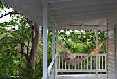 Hängematte in der Abendsonne auf der über Eck geführten Holzveranda eines Strandhauses, umgeben von Bäumen & Grünpflanzen
