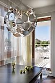 Schalensitze aus klaren Acrylglas an modernem Esstisch und Leuchtenklassiker Dandelion vor Fensterfront mit Blick auf den Balkon