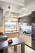 Elegant capiz shell pendant lamp above dining table in small fitted kitchen in shades of beige and grey