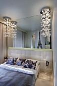 Sophisticated bubble lamps flanking French bed with upholstered headboard and photo-prints on scatter cushions against mirrored wall