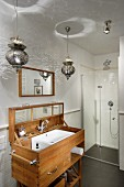 Oriental pendant lamps above custom-made washstand with lid and floor-level shower in background