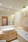 Florales Fliesenmosaik hinter Badewanne und Quasten an den Schubladen eines Wachtisches mit ovalem Becken