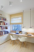 Spherical chrome lamps above narrow desk and Eames chairs with bookshelves to one side and Roman blind on window
