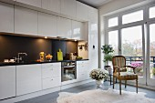 Eclectic interior with black and white, glossy kitchen counter and splashback, antique armchair and modern glass wall