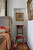 Icon and antique chair in niche next to bed with upholstered headboard and traditionally patterned bed linen