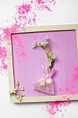 Two Star-of-Bethlehem flowers (Ornithogalum) with bulbs in taffeta bag tied with ribbon on lilac surface scattered with coloured powder