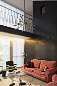 Traditional sofa with brocade pattern and delicate, curved metal coffee table against black stucco lustro wall in modern interior with gallery and fifties-style pendant lamp