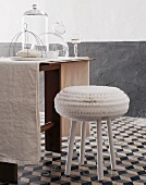 White stool on grey and white floor tiles at table with glass covers and glass of white wine