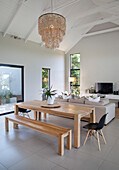 Wooden dining table and bench in bright, open-plan living area