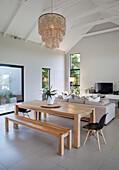 Heller, offener Wohnbereich mit Esstisch und Bank aus Holz