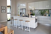 Island counter with bar stools and pale fitted kitchen in open-plan interior