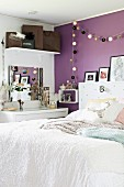 Bed with white bedspread in modern bedroom with string of lanterns hung on purple-painted wall