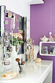 Makeup brushes on white console table below mirror with lights along both sides; purple-painted wall in background