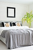 Pale grey blanket and scatter cushions with gold CND symbols on double bed; potted plant against white wood-clad wall to one side