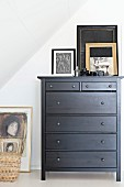 Picture and picture frame on top of black-painted chest of drawers under sloping ceiling