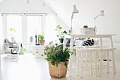 White counter and stools next to plant in wicker planter on pale floor and lounge area in background in converted attic