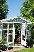 Greenhouse made from recycled materials in summery garden