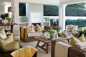 Wicker furniture and yellow and green accents in seating area on roofed patio