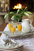 Tray of orange juice in front of vase of lilies on dining table
