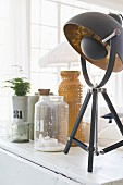 Table lamp with black and gilt lampshade next to vintage glass and ceramic vessels