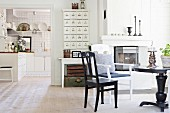 Runder, schwarzer Tisch mit Stühlen vor Kaminofen, seitlich offener Durchgang und Blick in die Küche