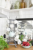 Cups hung on metal bottle rack and bowl of fresh radishes on wooden worksurface in corner of kitchen