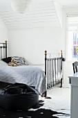 Vintage Metallbett mit grauer Tagesdecke in Dachzimmer mit weisser, holzverkleideter Decke