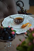 Place setting with white plate, glass teacup and saucer and cake on glass plate