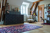 Rug on wooden floor in front of vintage chest of drawers next to window and armchair in corner
