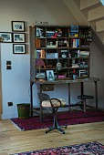Metal chair at vintage metal bureau with shelves below staircase