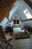 Bed and antique folding chair in converted attic with rustic wooden beams and pitched roof