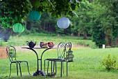 Tisch und Stühle aus gebogenem Metall unter Kastanienbaum mit Lampions
