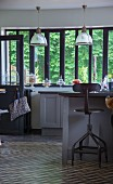 Vintage swivel chair at kitchen counter, bank of windows with frames painted dark grey and view of garden