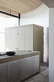 Concrete kitchen counter with built-in cupboards in front of multifunctional cupboard with wooden surfaces stained pale grey