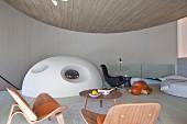 Extravagante Lounge in Kreisform davor massgefertigter Ofen mit Kaminfeuer als Halbkugel, im Vordergrund Klassikerstühle und Coffeetable aus Holz