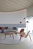 Klassikerstühle und Coffeetable aus Holz auf rundem Teppich vor massgefertigtem Sofa in Hellgrau, an gebogener Lounge Wand, seitlich Retro Stehleuchte