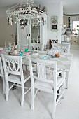 Mit Anhängern dekorierter Metallschirm über Tisch mit Schachbrettmuster und Spruchband, Sammlung weiss lackierter Holzstühle