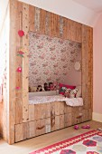 Cubby bed made from reclaimed boards in girl's bedroom with sloping ceiling