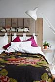 White retro standard lamp next to bed with vintage-style bedspread and headboard made from reclaimed boards
