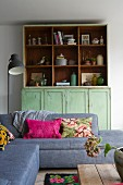 Grey sofa with scatter cushions in front of green dresser with shelving top section